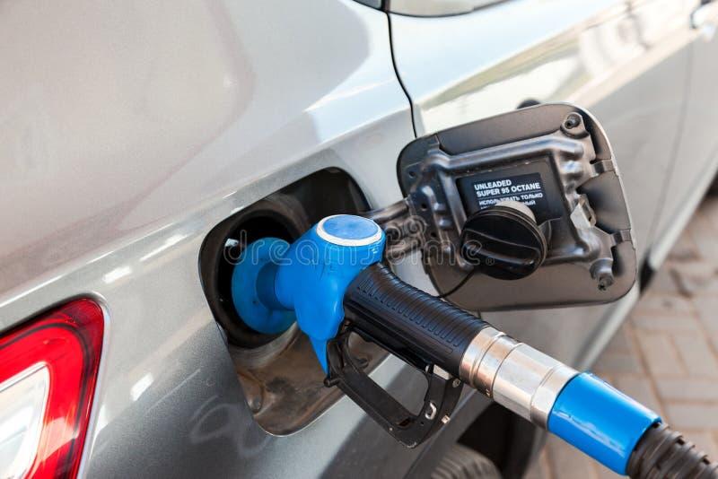 Surtidor de gasolina para lanzar el combustible en el vehículo de pasajeros en la gasolinera imagen de archivo