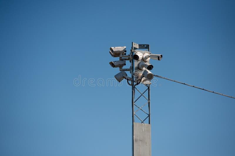 Surveilance cameras on a pylon. Surveilance cameras on a high pylon against a blue sky royalty free stock photography