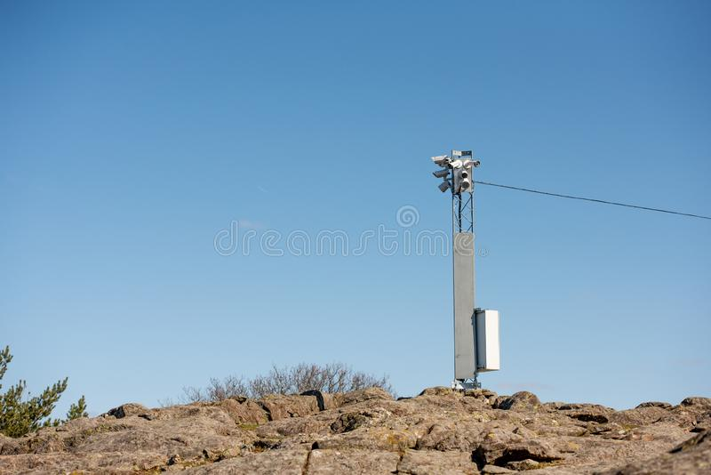 Surveilance cameras on a pylon. On a rocky hill. Blue sky in the background royalty free stock photos
