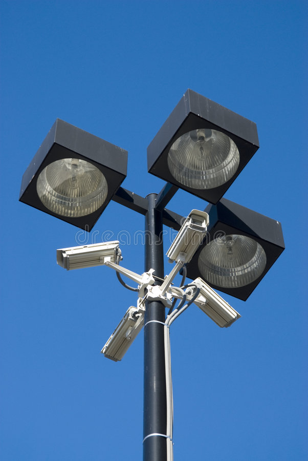 Surveillance cameras. Security cameras mounted on floodlights in a parking lot royalty free stock photography