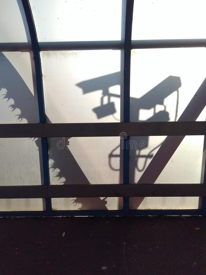 Urban surveillance silhouetted against translucent perspex wall. 2 stock photos