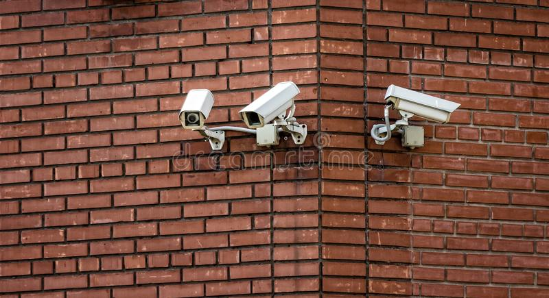 Surveillance cameras. Three surveillance cameras installed on the brick wall of the building royalty free stock photography