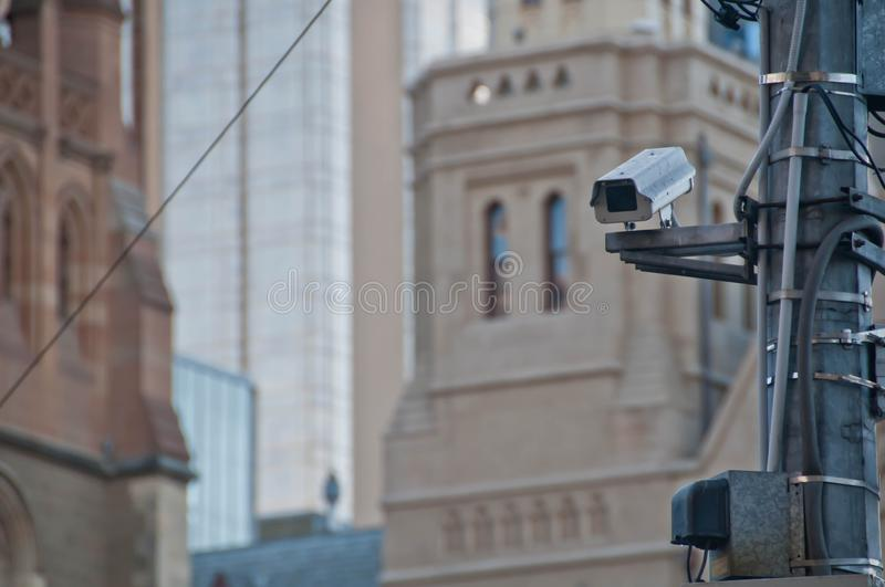 Surveillance CCTV street outdoor camera watching pedestrian near. European church in city center to prevent terrorism. The photo is taken in the afternoon royalty free stock image