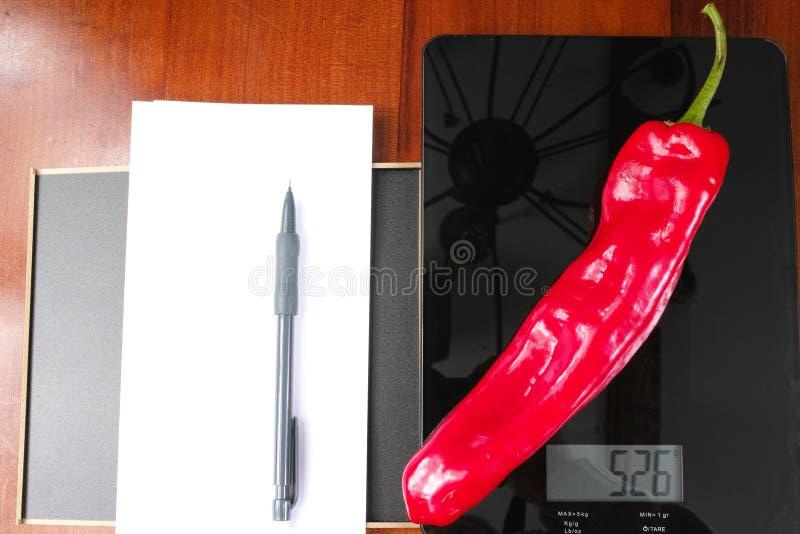 Surveillance du poids, échelle en verre noire de cuisine avec le paprika rouge, crayon et papier images stock