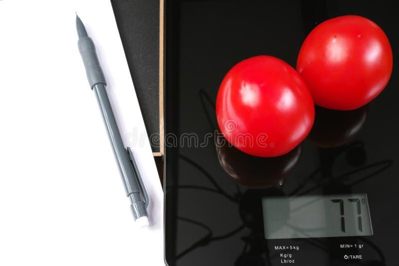 Surveillance du poids - échelle en verre noire de cuisine avec les tomates, le crayon et le papier rouges photographie stock libre de droits