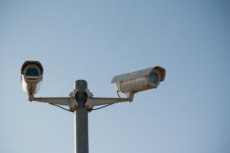 Surveillance. Two security surveillance cameras - one looking directly at the viewer, one directed elsewhere - against a faded blue sky stock photos