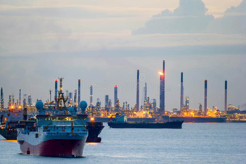 Survey and Cargo Ships off the Coast of Singapore Petroleum Refinery. Seismic survey vessel and cargo container ships off the coast of Singapore Island Petroleum royalty free stock image