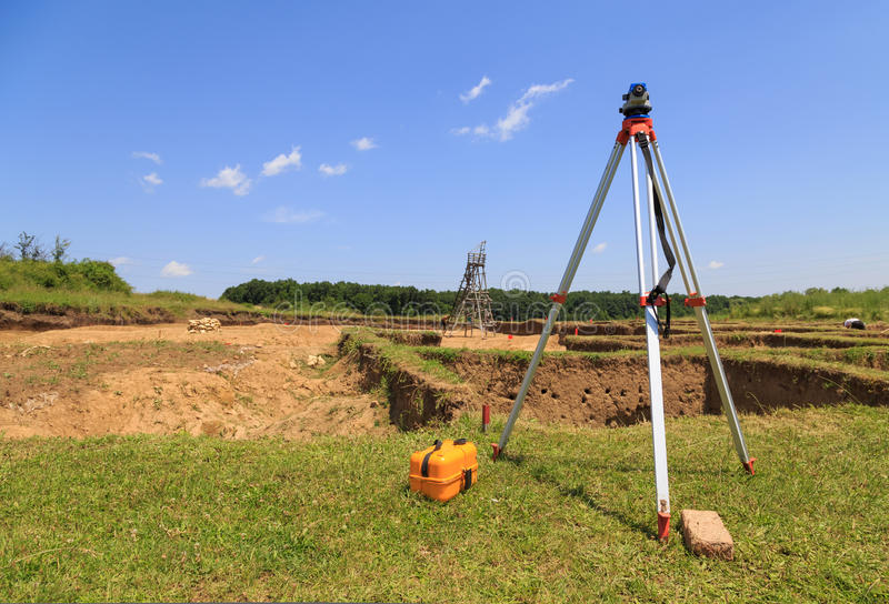 Surveying measuring equipment on tripod. At neolithic excavations site on field stock image