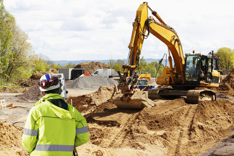 Surveyor, bulldozer and excavation works royalty free stock photos