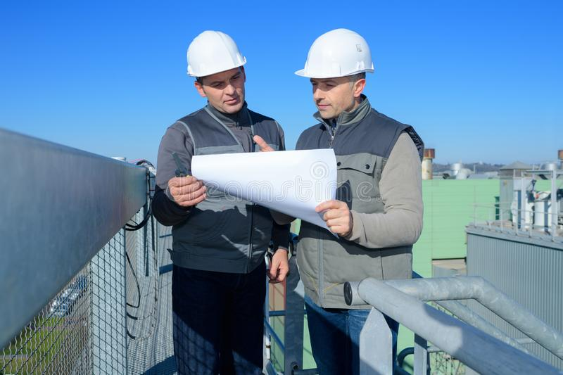 Surveyor and construction worker with plans on site royalty free stock image
