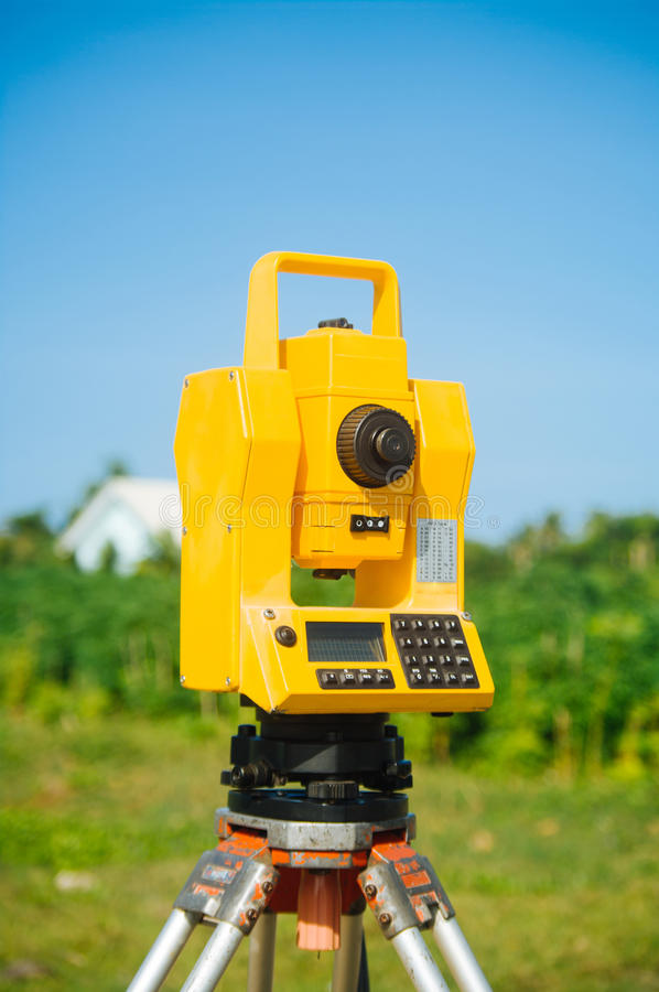 Surveyor equipment theodolite on tripod on future construction site royalty free stock image