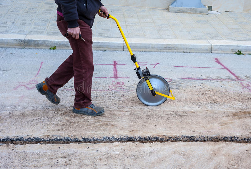 Surveyor with measuring wheel (odometer). Detects the length of an excavation of minitrench royalty free stock image