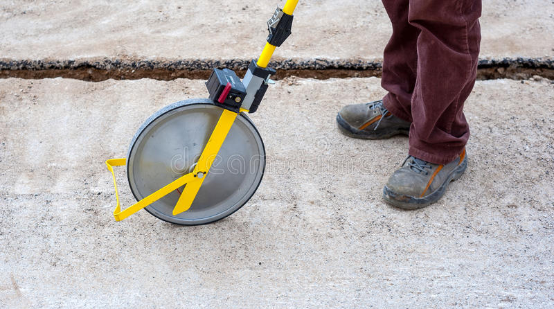 Surveyor with measuring wheel (odometer). Detects the length of an excavation of minitrench royalty free stock images