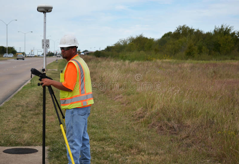 Surveyor In Safety Gear Working In The Field. Surveyor wearing a hard hat and safety vest using his equipment to survey a highway royalty free stock images