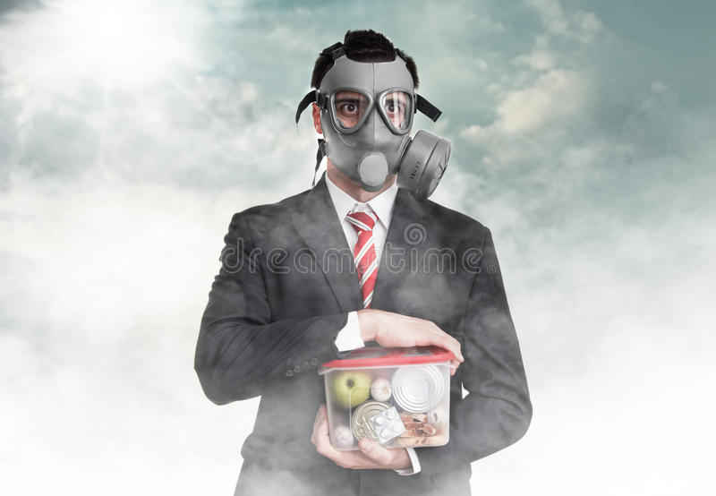 Survival. Business man with gas mask holding nutrition, survival concept stock photos