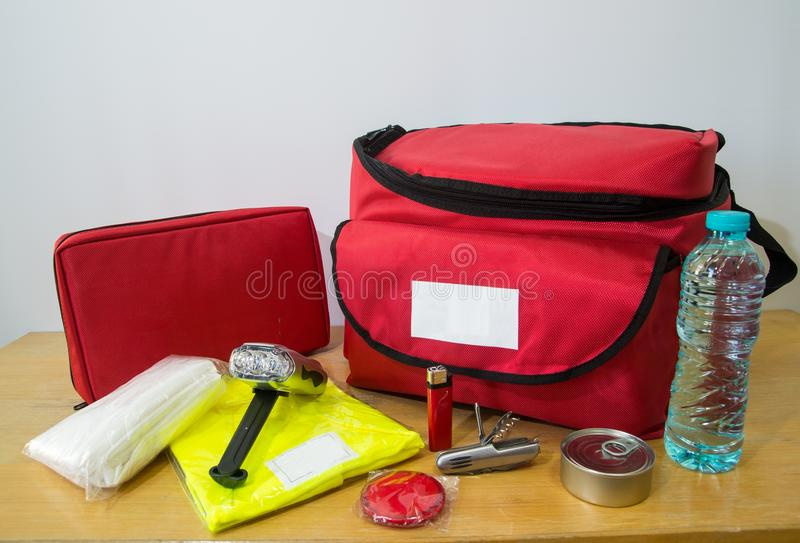 Survival kit. Emergency kit for survival in case of disaster including water, first aid kit, lighter, bags, utility knife and others stock photography