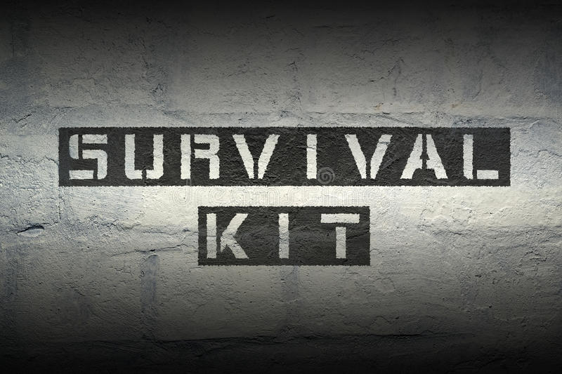 Survival kit GR. Survival kit stencil print on the grunge white brick wall stock images