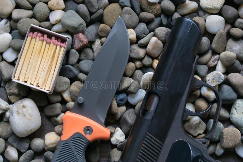 Survival kit for tough man. gun and knife. Survival kit for tough man. box of matches, folding knife and black gun on the rocks. top angle aerial shot royalty free stock photography