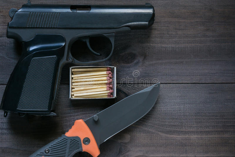 Survival kit for tough man. gun, knife, matches. Survival kit for tough man. box of matches, folding knife and black gun on dark brown background. top angle stock photography