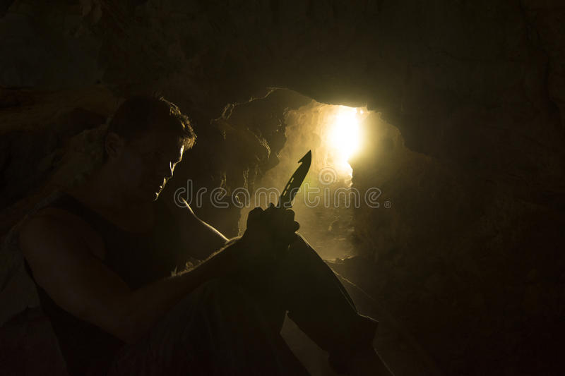 Survival man with knife backlit in dusty cave royalty free stock image