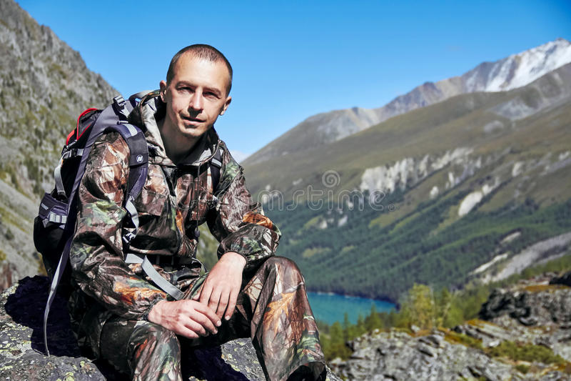 Survival in the wild. A man in camouflage resting among the mountains. Stalker, survive in the woods. Lake in the mountains. Snowy peaks, Altai royalty free stock photo