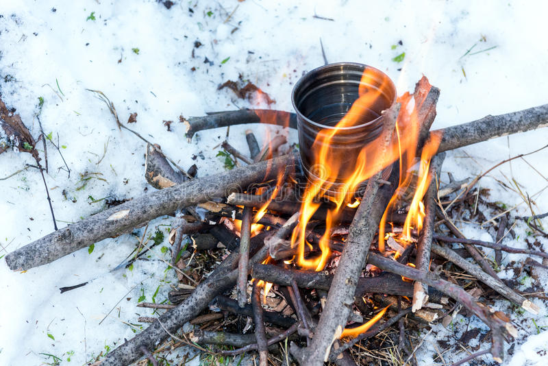 Survival in the winter. Boiling water for tea over small campfire royalty free stock images