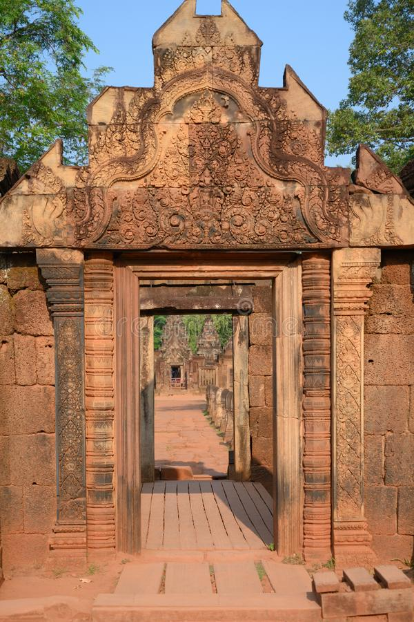 Survive of beautiful carved stone pillars and entrance of old temple in ruins of Banteay Srei, Cambodia. Survived entrance in badly maintainend temple of Banteay royalty free stock photo
