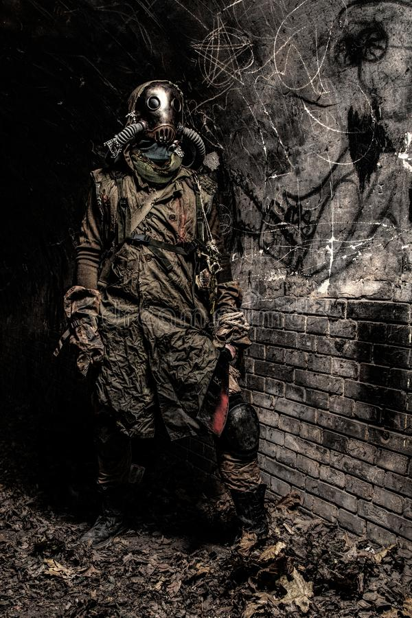 Living underground post apocalyptic scary creature. Survived in nuclear disaster or global ecological catastrophe human wearing rags, gas mask or air breathing royalty free stock image