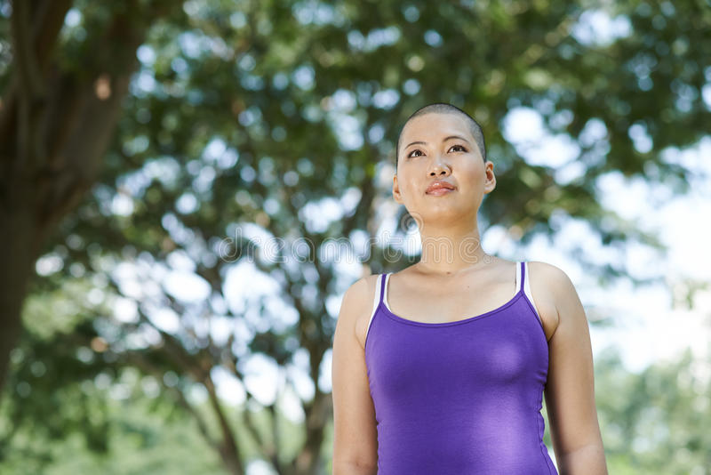 Surviving breast cancer. Portrait of woman exercising in park after surviving breast cancer royalty free stock image