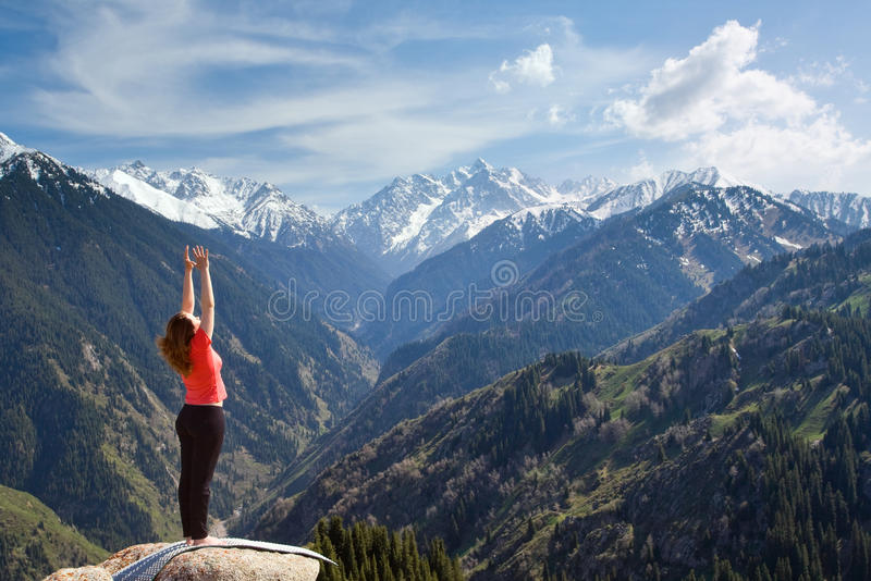 "Surya Namaskara - Sun Salutation is a common sequence of Hatha y. The young woman is doing a yoga asana ""Sun Salution"" on the summit. On the stock photography"