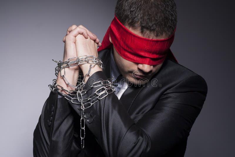 Sus manos están en cadenas y se vendan los ojos de sus ojos fotografía de archivo libre de regalías