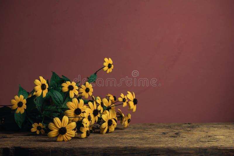 Susans ornés de noir sur une vieille table en bois de chêne sur fond de mur rouge photographie stock libre de droits