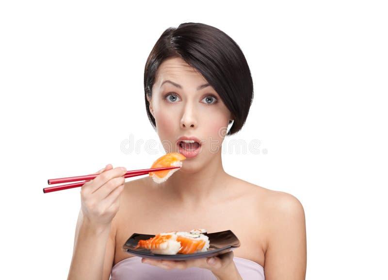 Sushi étonnés de fixation de jeune femme photos stock
