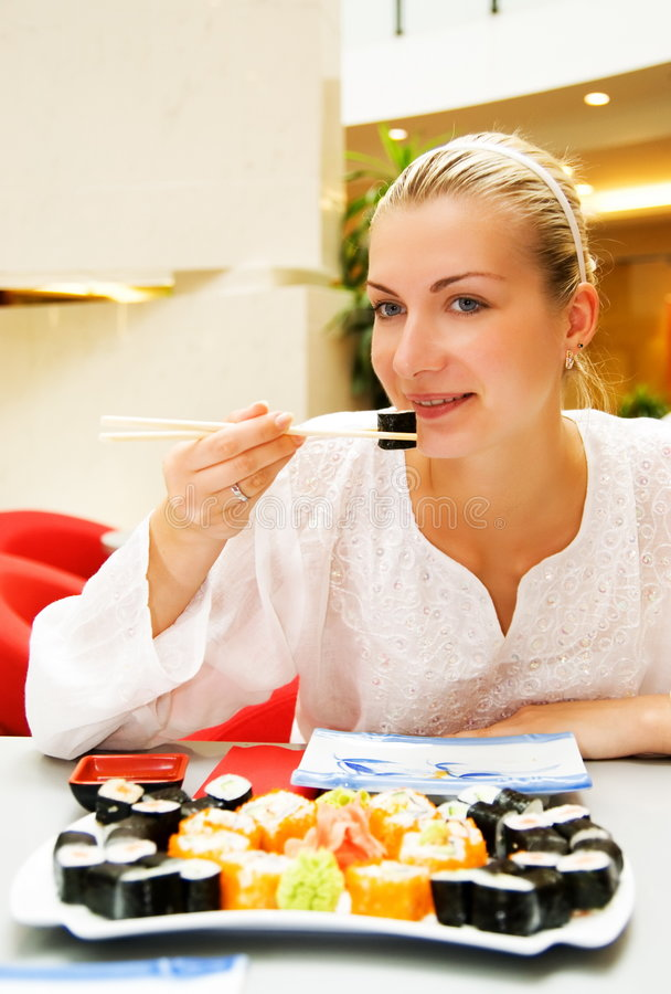 Sushi. Picture of a beautiful girl eating sushi stock images