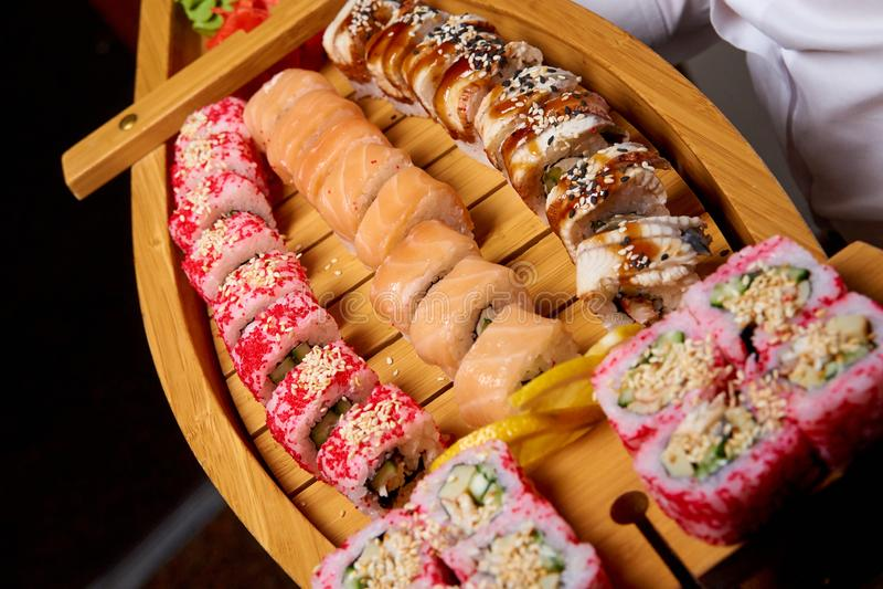 Sushi ajustado em um barco de madeira nas mãos do cozinheiro fotos de stock royalty free