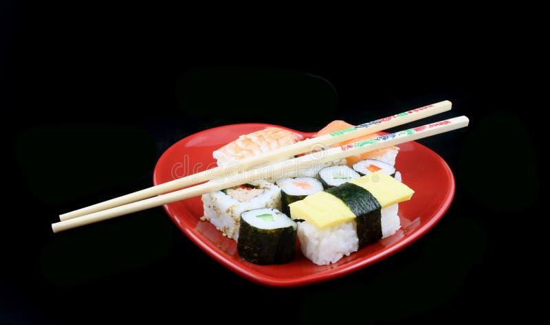 Sushi auf einem schwarzen Hintergrund mit Ess-Stäbchen stockbild