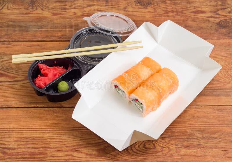 Sushi avec des saumons dans la boîte pour la nourriture à emporter, condiments image libre de droits