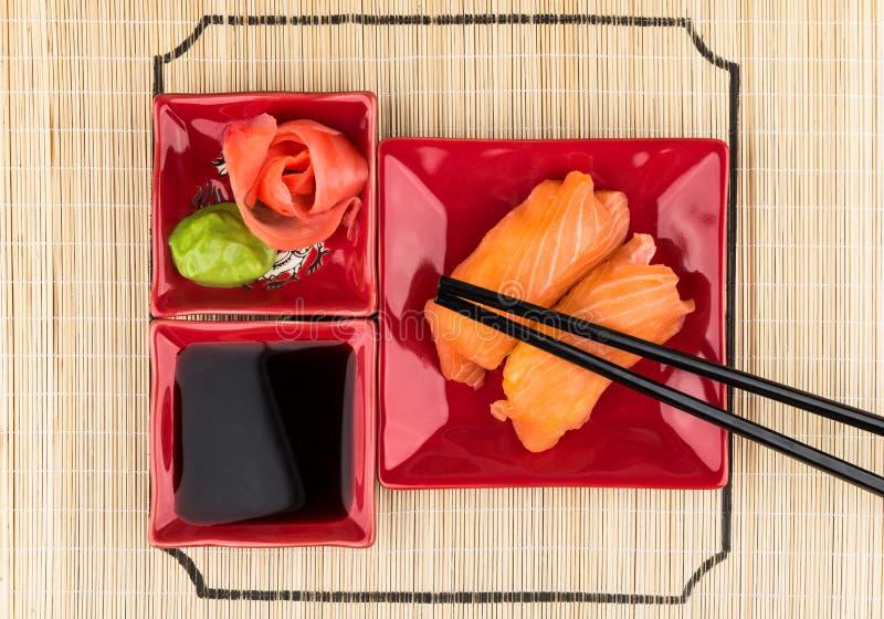 Sushi avec des saumons, sauce de soja, gingembre, wasabi sur le tapis en bambou image stock