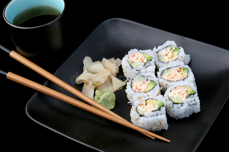Sushi avec du thé sur le noir images stock