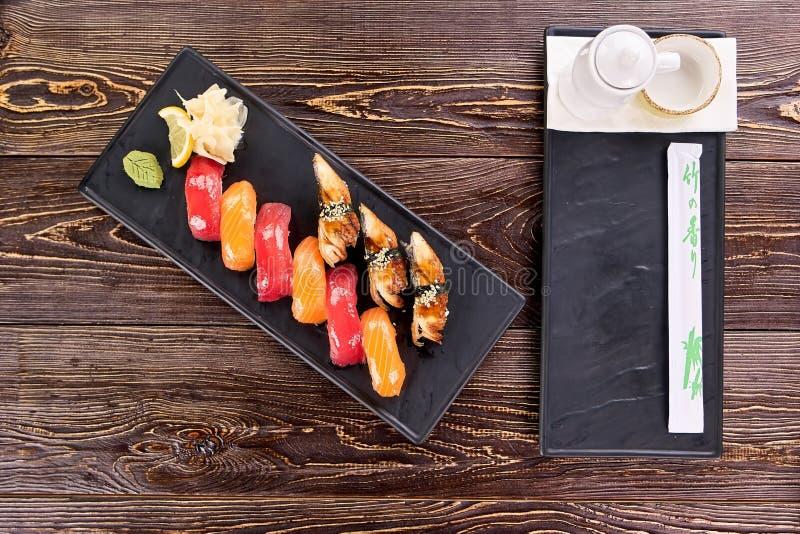 Sushi bagnati succosi di nigiri e piatto laterale, vista superiore immagini stock