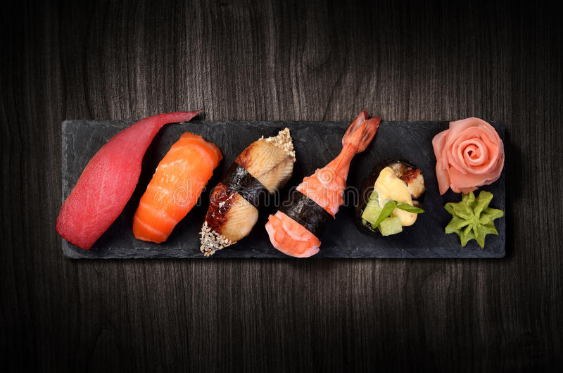 Sushi on black stone plate. Sushi on black stone slate plate, black wooden background stock photos