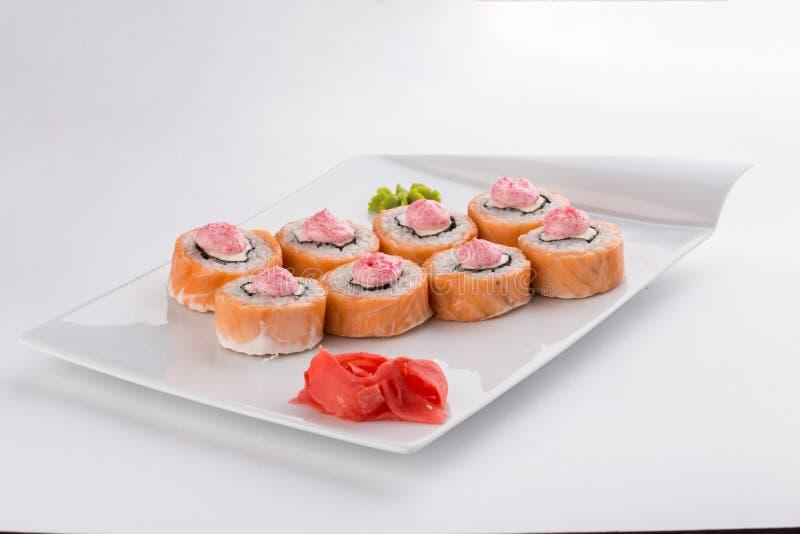 Sushi caldi del rotolo di Filadelfia con formaggio di color salmone e cremoso isolato su fondo bianco fotografia stock