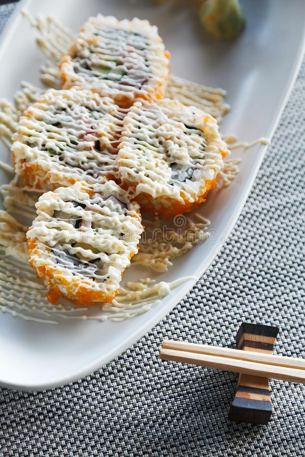Sushi california rolls with topping mayonnaise on matt and chopstick beside royalty free stock images