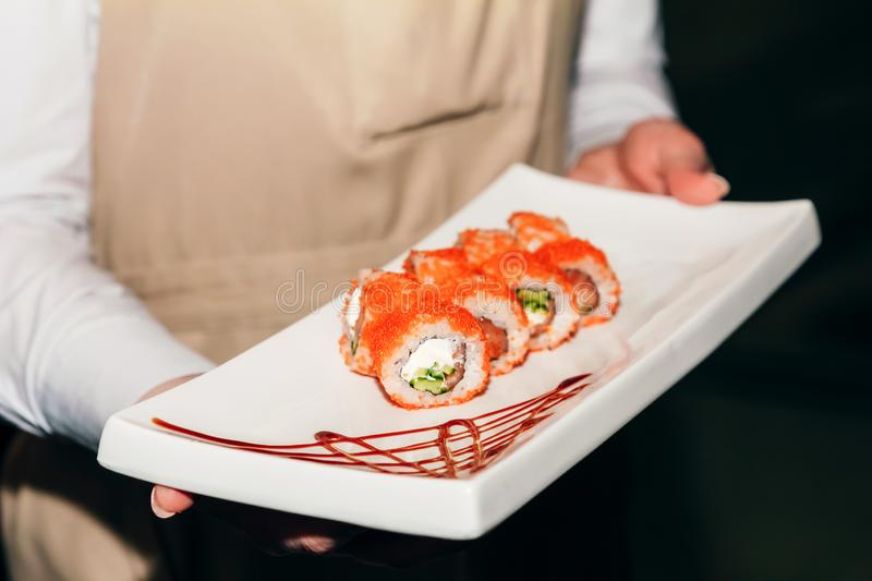Sushi california salmon on a white rectangular plate in the waiter`s hand close-up.  royalty free stock images