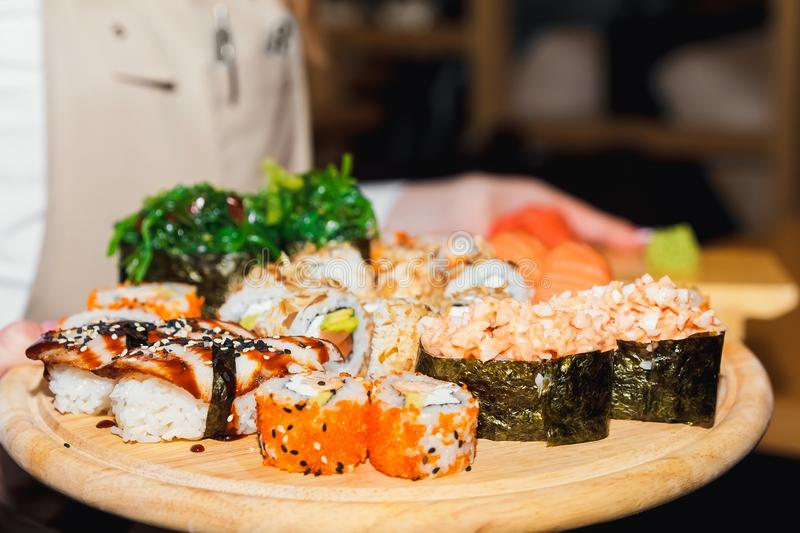 Sushi california salmon on a white rectangular plate in the waiter`s hand close-up.  stock images