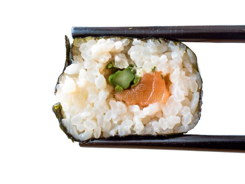 Sushi on a chopstick. Sushi on a black chopstick royalty free stock photo
