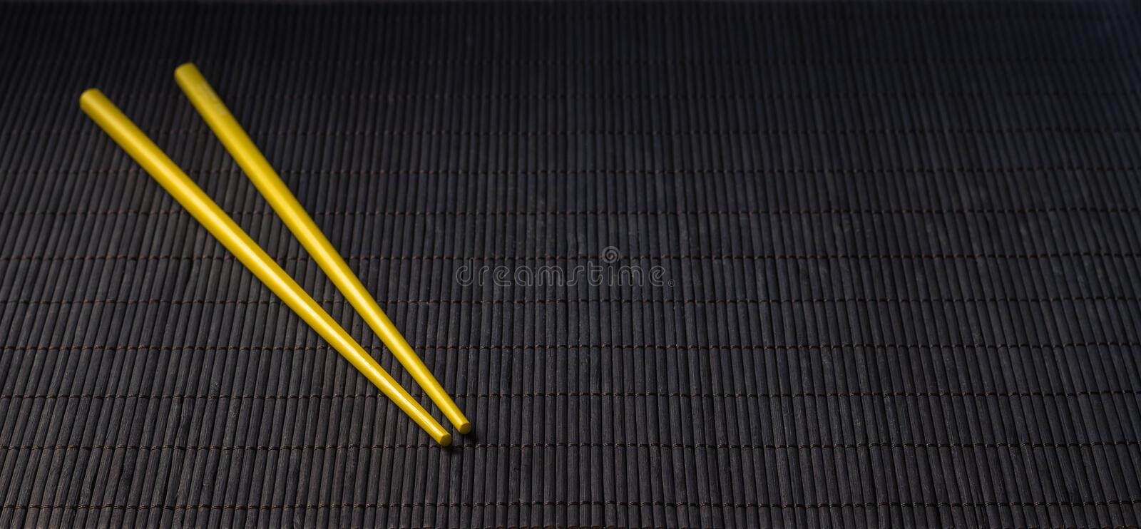 Sushi chopsticks on black bamboo straw mat. Yellow sushi chopsticks on black bamboo straw mat, space for text stock image