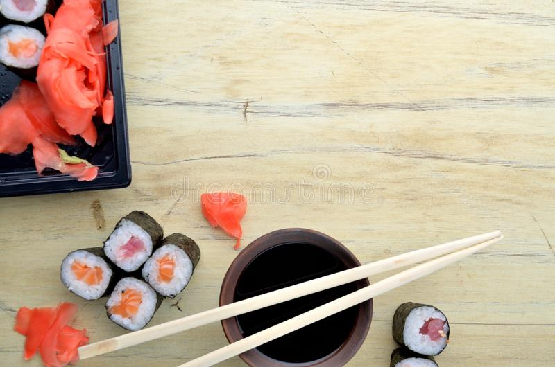 Sushi chopsticks over soy sauce bowl, salmon rolls stock images