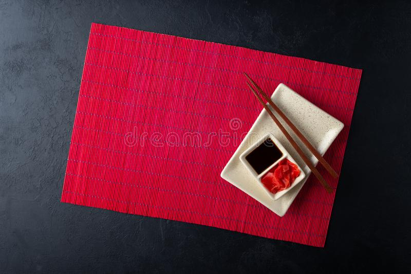 Sushi chopsticks, soy sauce, ginger, red bamboo mat and empty plate on black background. Top view. Flat lay royalty free stock images