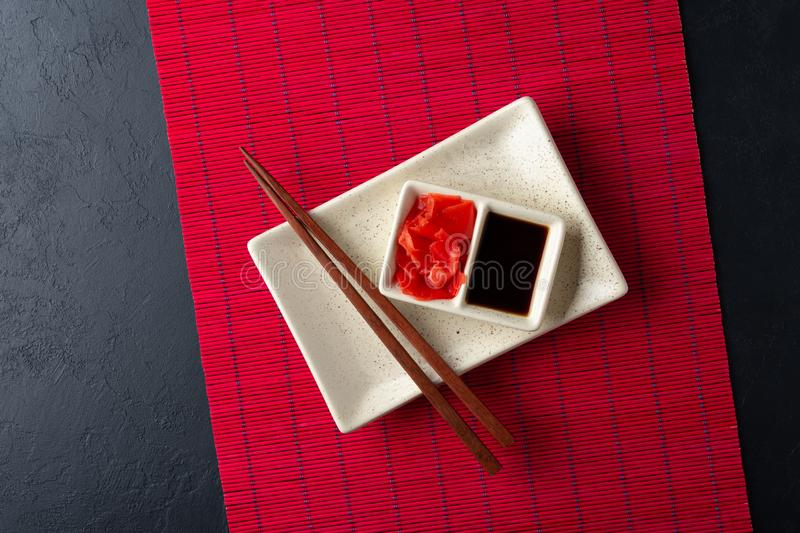 Sushi chopsticks, soy sauce, ginger, red bamboo mat and empty plate on black background. Top view. Flat lay stock photography